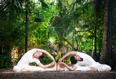 14101499-couple-yoga-of-man-and-woman-in-white-cloth-doing-parivrtta-janu-sirsasana-revolved-head-to-knee-pos